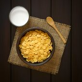 stock photo of cereal bowl  - Crispy corn flakes breakfast cereal in rustic bowl with a glass of milk and a wooden spoon on the side photographed overhead on dark wood with natural light - JPG