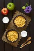 picture of cereal bowl  - Crispy corn flakes breakfast cereal in rustic bowls with glasses of milk apples wooden spoons and flower on the side photographed overhead on dark wood with natural light - JPG