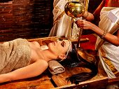 picture of panchakarma  - Young woman having pouring oil Ayurveda spa treatment - JPG