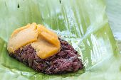 stock photo of custard  - Black Sticky rice with custard wrapped in banana leaves - JPG