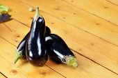 foto of brinjal  - view of three eggplants on wooden kitchen table - JPG