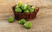 stock photo of brussels sprouts  - Basket of fresh green brussels sprouts on wooden background - JPG