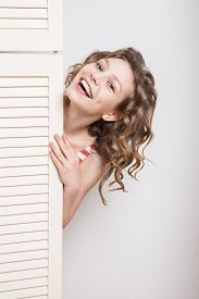 picture of jalousie  - Beautiful young woman looks around edge of a jalousie - JPG