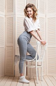 pic of jalousie  - Beautiful woman wearing pants and shirt sitting on a chair in front of a jalousie - JPG