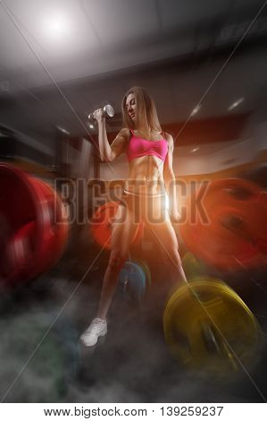 poster of Fitness woman standing in a smoky gym. Fitness woman in the gym. fitness girl with dumbbell posing in the gym. Fitness - concept of healthy lifestyle. Perfect fitness body.