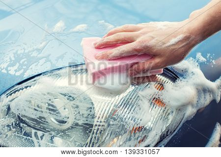 poster of Washing the car by hand with soapy sponge. Cleaning the car. Car care concept. Hand of man washing the car using the sponge with foam