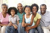 image of extended family  - Extended Family Relaxing On Sofa At Home Together - JPG