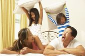 stock photo of pillow-fight  - Young Family Having Pillow Fight In Bedroom - JPG