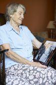 Постер, плакат: Старший женщина в доме глядя на старые свадебное фото