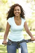 stock photo of middle-age  - Woman Riding Bike In Park - JPG