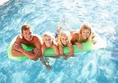 stock photo of family fun  - Family Outside Relaxing In Swimming Pool - JPG