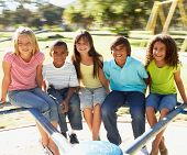 foto of playground  - Group Of Children Riding On Roundabout In Playground - JPG