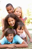 stock photo of children group  - Group Of Children Piled Up In Park - JPG