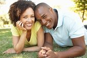 foto of mixed race  - Portrait Of Young Couple Laying On Grass In Park - JPG