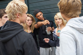 stock photo of underage  - Group Of Threatening Teenagers Hanging Out Together Outside Drinking - JPG