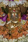 pic of lakshmi  - Silver idol of deity Lakshmi copiously decorated with flowers - JPG