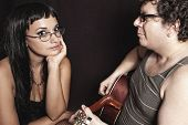 foto of serenade  - man singing a love serenade on guitar to a beautiful woman in eyeglasses against dark background - JPG