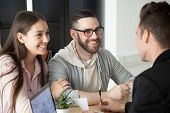 Excited Smiling Millennial Couple Discussing Mortgage Loan Investment Or Real Estate Purchase With R poster