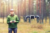 Man Flying Drone In The Woods. Focus On Drone poster