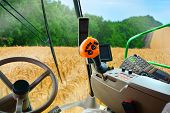 Combine Harvester Harvests Wheat. View From A Salon Of A Hi Tech Harvester. poster