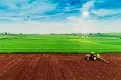 Aerial Shot Of  Farmer With A Tractor On The Agricultural Field Sowing. poster