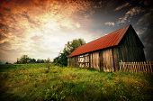 stock photo of wooden shack  - Old wooden bar with red roof over the dramatic sunset - JPG