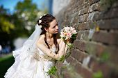 Russian Bride With Wedding Bouquet Near Old Castle