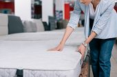 Partial View Of Woman Touching Orthopedic Mattress In Furniture Shop poster