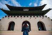 Постер, плакат: Young Asian Woman Traveler With Backpack Traveling Into The Gyeongbokgung Palace With Blue Sky And