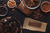 Chocolate Background. Milk Chocolate Bar, Candies, Raisins, Almonds And Cocoa Bowls On Black Table,  poster