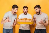 Three young excited men holding a big pizza isolated over yellow background poster