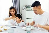 Asian Parents Feeding Their Child And The Whole Family Having Meal Together At Home poster