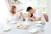 Happy Asian Family Of Father, Mother And Son Playing And Laughing While Having Dinner poster