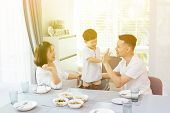 Happy Asian Family Is Giving High Five With Each Other While Having Dinner At Home poster