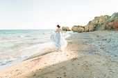 Fashion Bride In Luxury Wedding Dress With Bouquet At The Sea Side. Wedding By The Sea. Bride Walkin poster