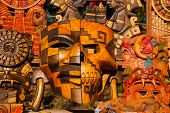 Mexican Souvenirs Made Of Wood In The Market For Tourists. Masks Tribe Maya, Skulls, Figurines And A poster