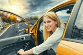 Beautiful Blonde Girl Driving A Car On The Highway. The Woman Opens The Car Door. Invitation To Trav poster