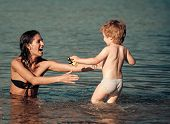 Cute Child Boy Play With Mom In Sea, Ocean. Mom And Kid With Smiling Faces Spend Time Together In Se poster