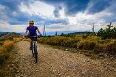Cycling, mountain biking woman on cycle trail in autumn forest. Mountain biking in autumn landscape  poster