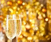 image of champagne color  - Two glasses of champagne with lights in the background - JPG