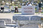 Tourists milling around the ruins of the Oeatpon Theatre on the island of Delos, Greece.