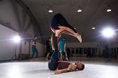Couple Does Acroyoga, Physical Practice Yoga And Acrobatics. Balance And Concentration Couple. Men A poster