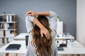 Close-up Of A Young Businesswoman Stretching Her Arms At Workplace poster
