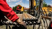 foto of crude  - Oil drilling rig workers lifting drill pipe - JPG