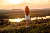 Back View Of Young Female With Long Hair Standing On Grass Near River And Admiring Cloudy Sundown Sk poster