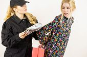 Shoplifting Is A Crime. Young Fashionable Woman Being Caught On Stealing Clothes By Female Security  poster
