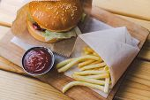 Fresh Tasty Burger And French Fries On Wooden Table. French Fries And Bbq Sauce On Wood Plate. Stree poster
