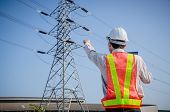Electrical Engineer Holding And Using A Digital Tablet, Engineer Pointing At High Voltage Power Pylo poster