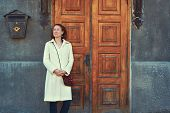 Young Smiling Woman In Coat Standing Over Yellow Old Fashioned Historical Wooden Door, Rusty Postbox poster