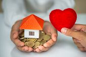 Orange Roof Houses And Coins In The Hands Of Business People. Red Heart Delivered Along The House. T poster